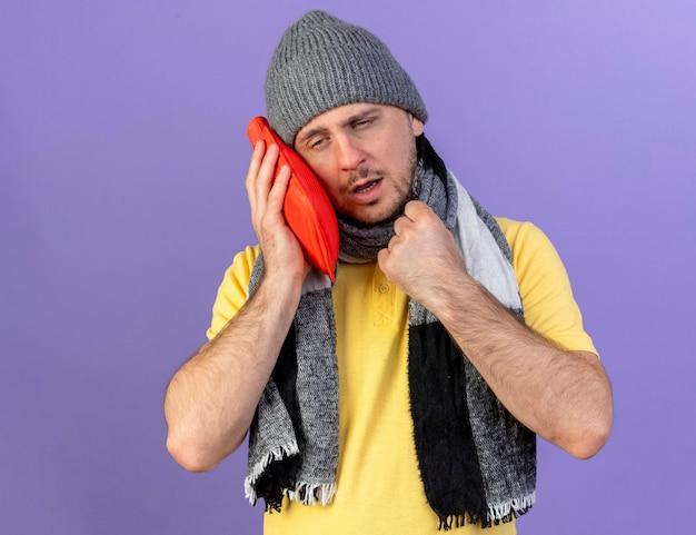 겨울 모자와 스카프를 착용 창백한 젊은 금발의 아픈 슬라브 남자