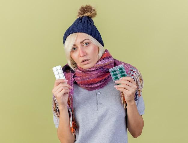 冬の帽子とスカーフを身に着けている淡い若いブロンドの病気のスラブ女性は、コピースペースでオリーブグリーンの壁に分離された医療薬のパックを保持します