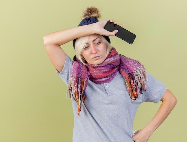 冬の帽子とスカーフを身に着けている淡い若い金髪の病気のスラブ女性は、コピースペースでオリーブグリーンの壁に分離された電話を保持している額に手を置きます