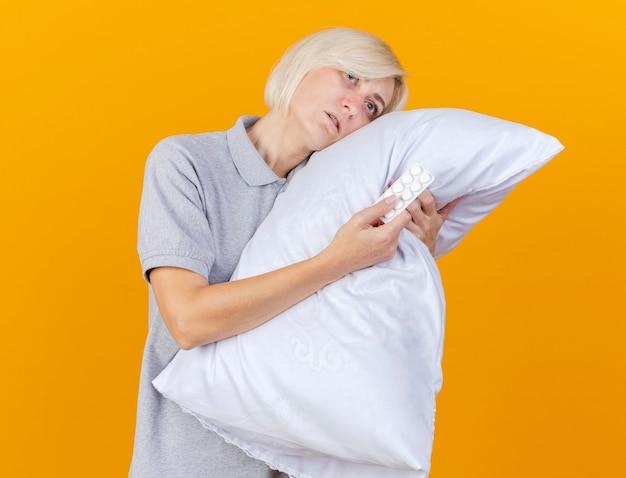 La giovane donna bionda malata pallida mette la testa sul cuscino tiene il pacchetto delle pillole mediche isolate sulla parete arancione