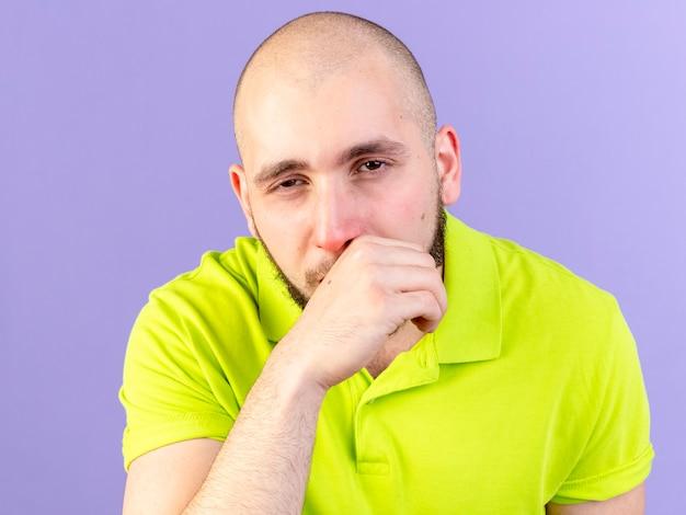 Pallido giovane uomo malato caucasico tosse isolato sulla parete viola con spazio di copia