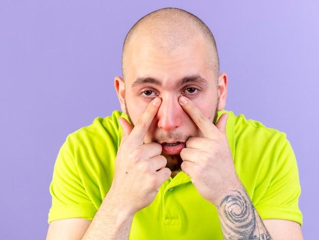 淡い若い白人の病気の人は、コピースペースで紫色の壁に隔離された鼻に指を置きます
