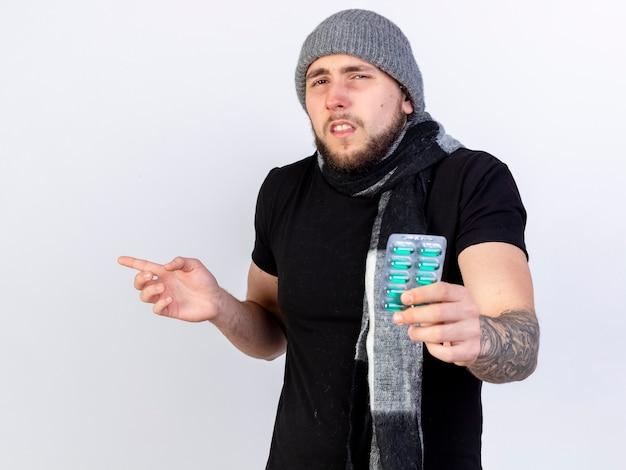 겨울 모자와 스카프를 착용하는 창백한 젊은 백인 아픈 남자는 의료 캡슐 팩을 보유하고 복사 공간이 흰 벽에 고립 된 측면에서 포인트