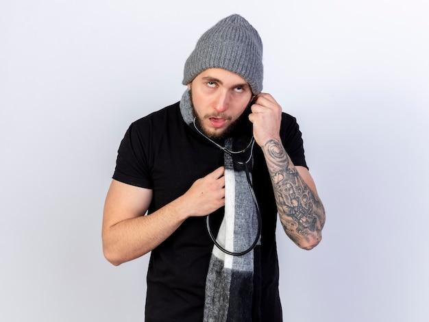 冬の帽子とスカーフを身に着けている淡い若い白人の病気の人は、コピースペースで白い壁に隔離された聴診器を保持します