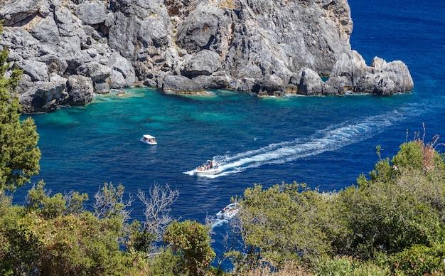 ギリシャ、コルフ島のパレオカストリッツア湾ボートに乗って休暇を楽しんでいる人々