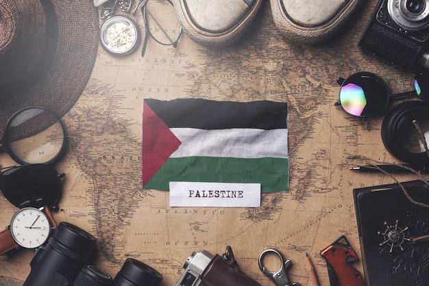 Palestine flag between traveler's accessories on old vintage map. overhead shot