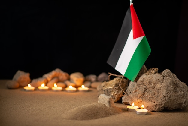 Palestinian flag with stones and burning candles on dark surface