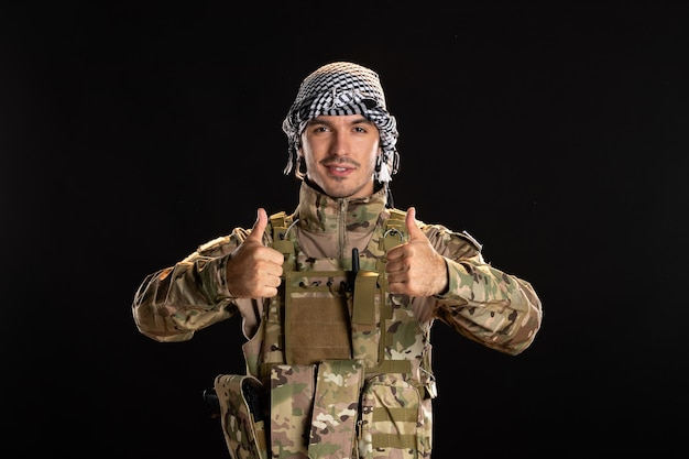 Palestinian serviceman in military uniform smiling on black wall