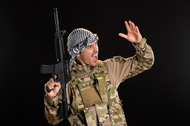 Palestinian serviceman in military uniform with rifle on dark wall