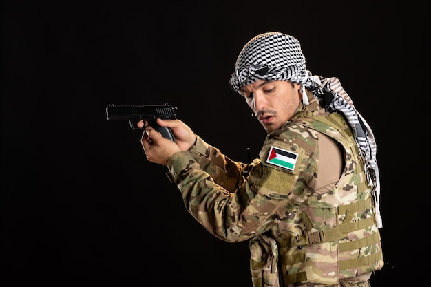 Palestinian soldier aiming gun on the black wall