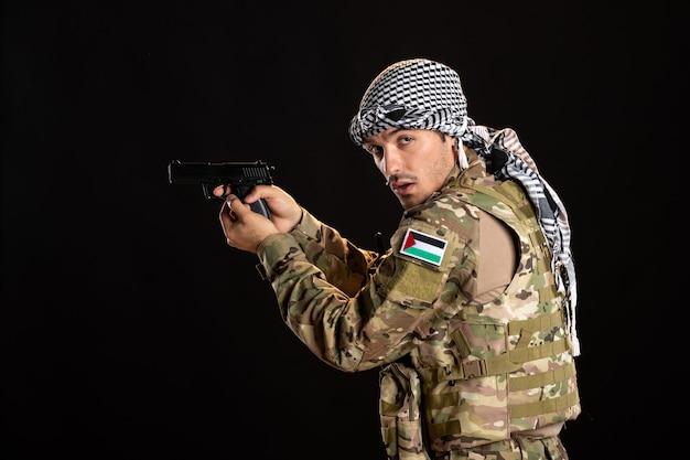 Палестинский солдат направляет пистолет на черную стену