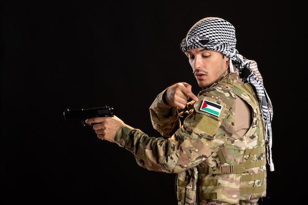 검은 벽에 총을 목표로하는 팔레스타인 군인