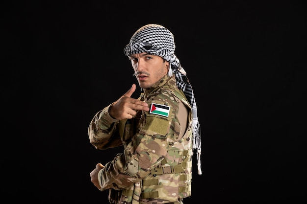 Palestinian soldier in camouflage on black wall