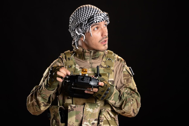 Palestinian soldier fixing remote controller on black wall