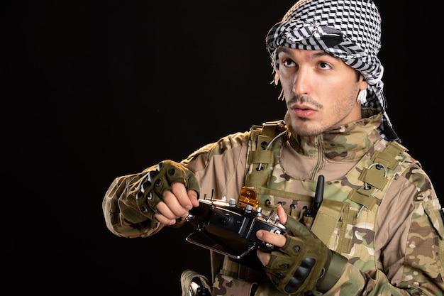 검은 벽에 원격 컨트롤러를 고정하는 팔레스타인 군인
