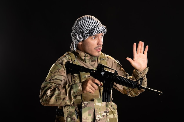 검은 벽에 기관총과 싸우는 위장에 팔레스타인 군인