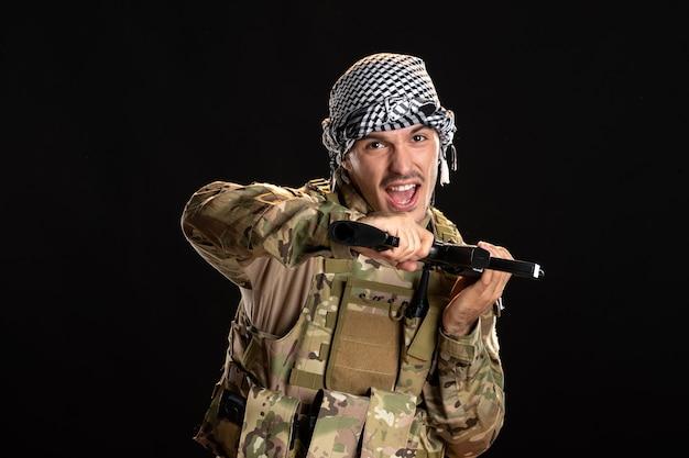 Палестинский солдат в камуфляже с пулеметом на черной стене