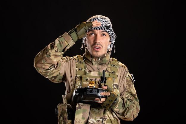 Soldato palestinese che usa il telecomando sul muro nero