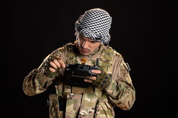 검은 벽에 리모컨을 사용하는 팔레스타인 군인