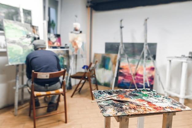 パレットとブラシは、椅子と塗料に座っている画家の背景の上に立つ