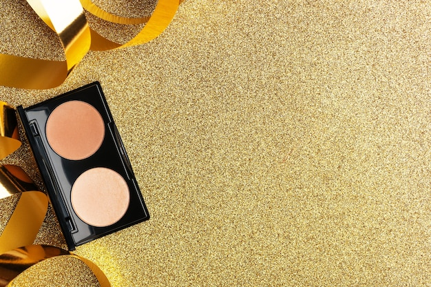 A palette of beige powder for professional makeup female face. a festive gift for a woman. beauty trendy cosmetic product for perfect skin tone on golden background with glitter top view. copy space.