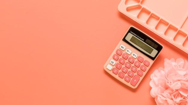 Палитра, калькулятор и лук на красном фоне