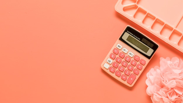 Palette, calculator and bow on red background