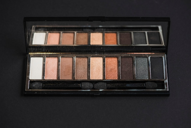 Palette of colorful eyeshadow on black background