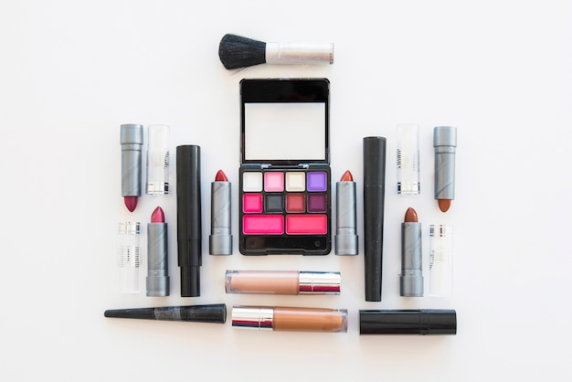 Palette of cosmetic eye shadow; different shades of lipstick; and brush on white backdrop