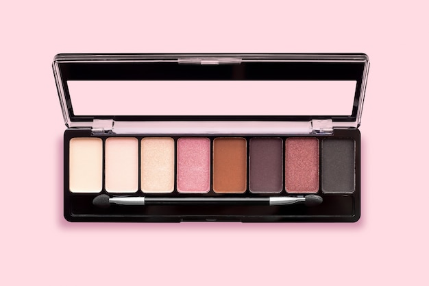 Palette of eyeshadows in brown tones, matte and shimmer eyeshadows on a pink background, top view. autumn eyeshadow palette with 8 colors, beige, red, brown, black