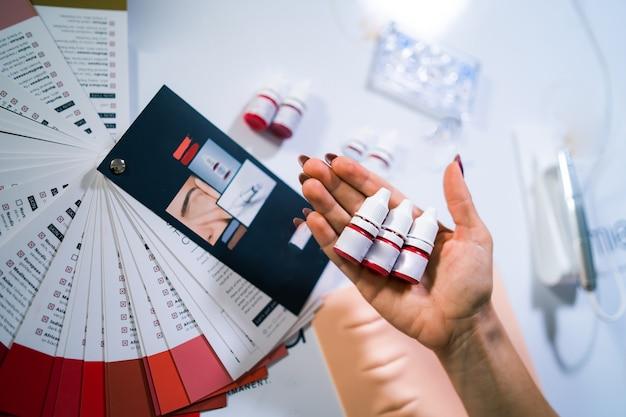 주인의 손에 영구적인 문신을 위한 팔레트. 입술 토닝을 위한 다양한 색상. 영구적인 문신을 위한 다채로운 빨간색 잉크가 있는 병. 전문 영구 문신 교육 자료. 확대.
