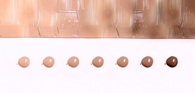 Palette of foundation creams of different colors, droplets on a light background