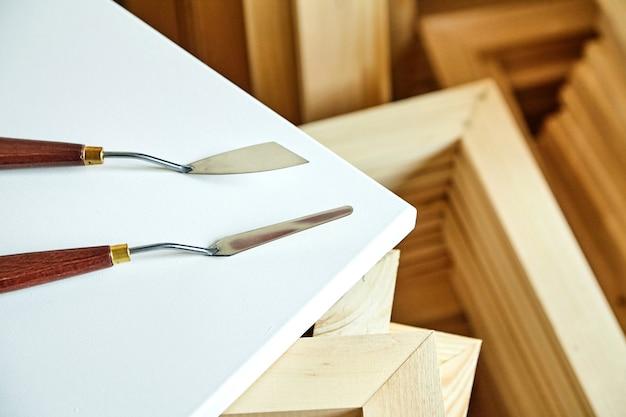 白い空白のコットンキャンバスと木製のストレッチャーバーの上に横たわるパレットナイフ