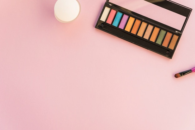 Palette of make up with brush over colored background