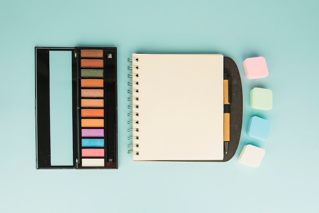 Palette of make up with colorful sponge and blank spiral notepad on colored backdrop