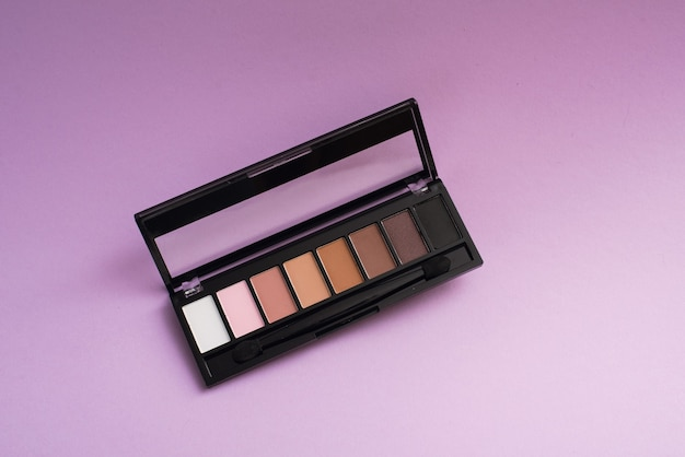 Палитра основных теней на фиолетовом фоне. концепция макияжа.