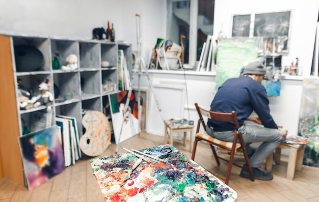 Palette of oil paints and brushes on the background of art studio