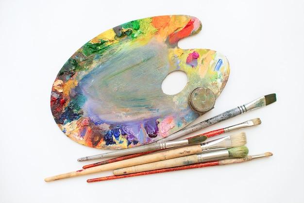 Палитра масляных красок, кистей на белом фоне. место для текста