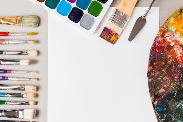 Palette and painting tools near paper