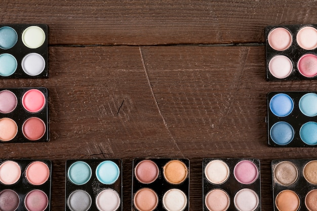 Palette of various eye shadow powder on wooden backdrop