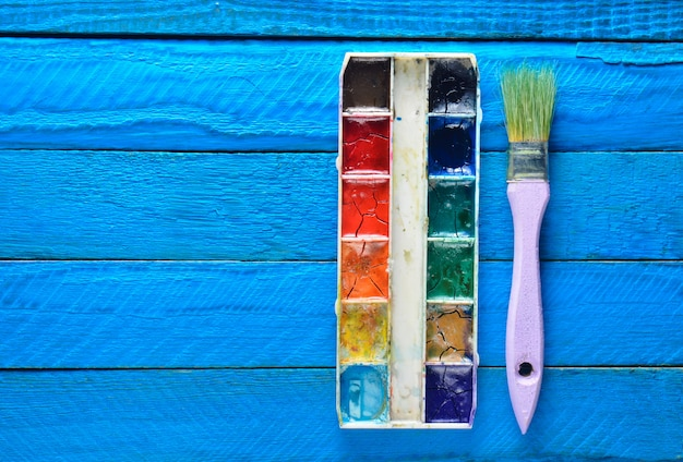 A palette of watercolor paint and a brush for painting on a blue wooden boards. top view. copy space. art concept.