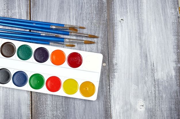 A palette of watercolor paints and brushes of different sizes, lying on a gray wood