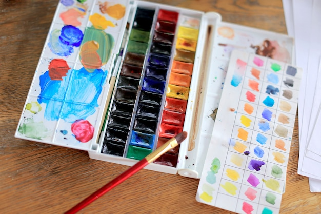 Palette of watercolor paints, brushes on wooden table