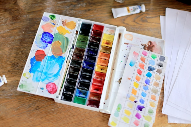 Palette of watercolor paints, brushes on wooden table,