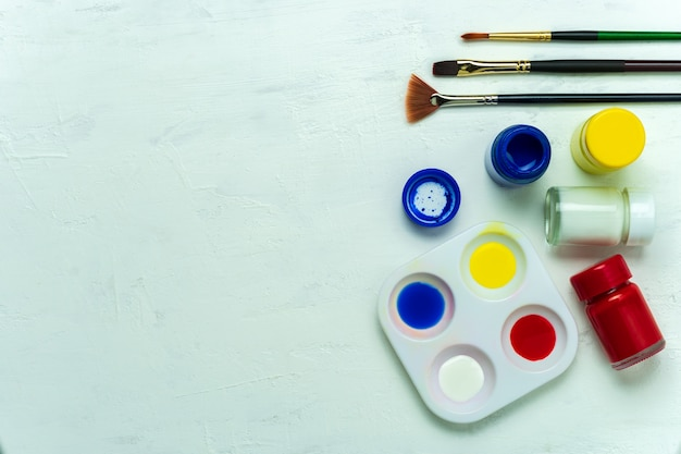 Palette and watercolor with paint brush on white background