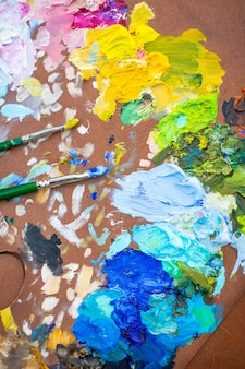 Palette with multicolored paints and brushes woman painting picture