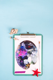 Palette with old paint strokes on clipboard with seashells