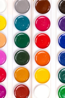 Palette with paints close-up lie isolated on yellow background