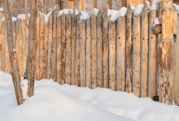 Paling, wooden fence made of logs in the village, winter