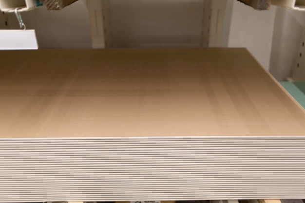 Pallet with drywall sheets plasterboard in the building warehouse store.